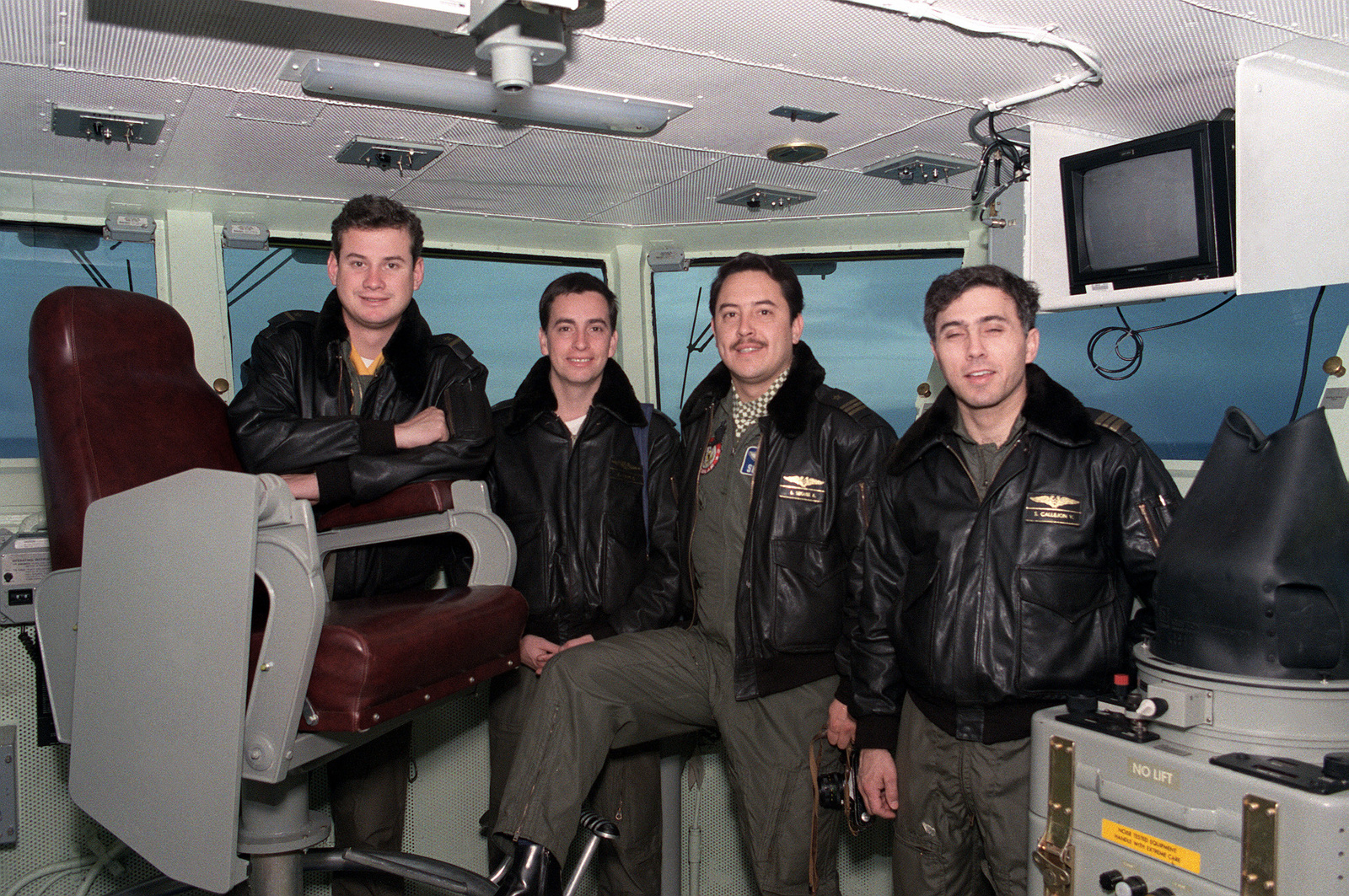Four Chilean officers stand beside the captain's chair on the bridge during a tour of the nuclear-powered aircraft carrier USS ABRAHAM LINCOLN (CVN-72). The LINCOLN is passing along the southern coast of Chile while en route to its new home port at Alameda, California