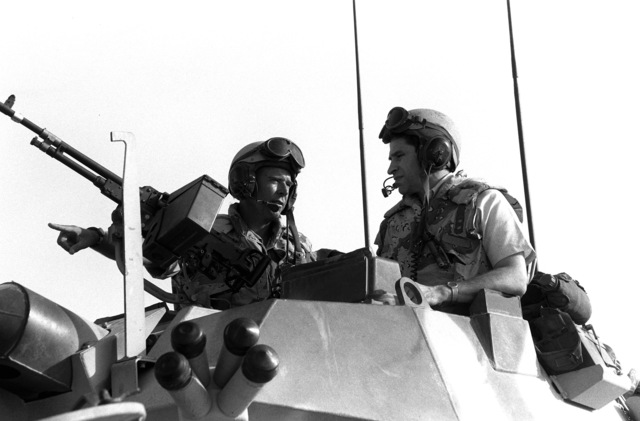 LT. COL. Cole, commanding officer of the 1ST Light Armored Infantry (LAI) Battalion, talks about the LAV-25 light armored vehicle with Undersecretary of Defense Doworitz during Operation Desert Shield.