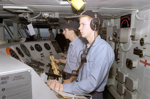 SA Todd Workman, foreground, monitors a sound-powered telephone circuit as SA Charles Rife mans the helm on the bridge of the nuclear-powered aircraft carrier USS ABRAHAM LINCOLN (CVN-72)