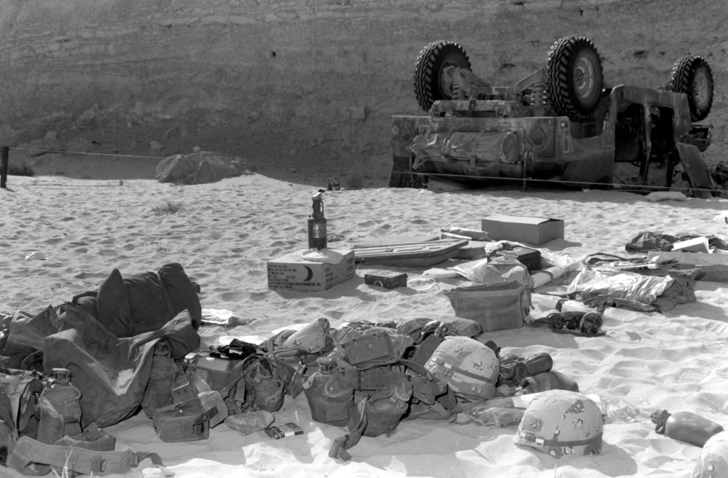 Gear from overturned M998 High-Mobility Multipurpose Wheeled Vehicle (HMMWV), lying on ground. Vehicle and cliff in background