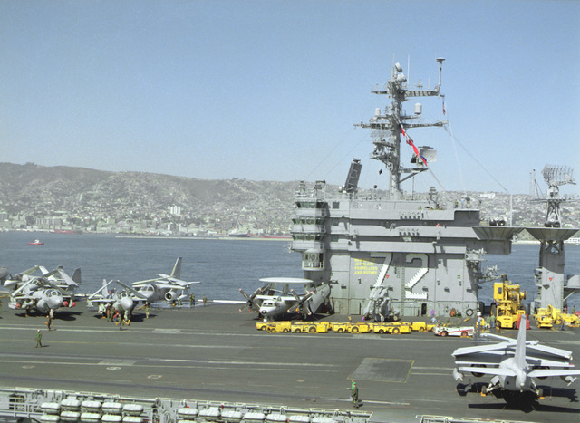 A view of the island of the nuclear-powered aircraft carrier ABRAHAM LINCOLN (CVN-72) as the vessel sits in port during a stopover while circumnavigating South America. MD-3A tow tractors and various aircraft are parked on the carrier's flight deck