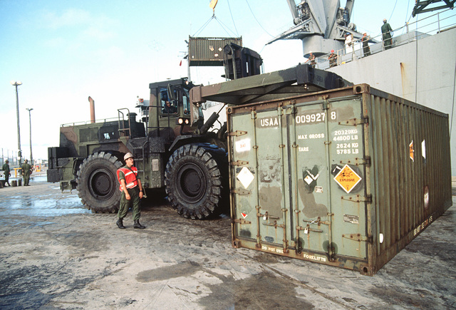 A rough-terrain container handler moves in to pick up a container of chemical munitions unloaded from a Military Sealift Command ship during Operation Steel Box. The munitions will be taken to the U.S. Army Chemical Activity on the atoll for storage and disposal