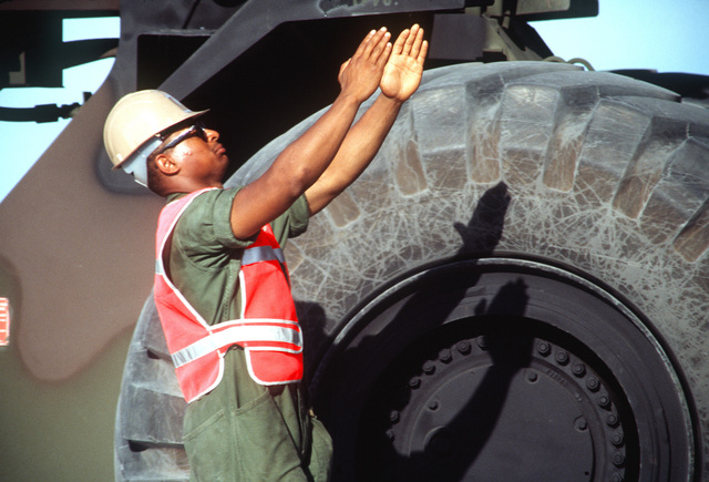 A soldier from the 155th Transportation Company directs a crane operator aboard a Military Sealift Command ship as he lowers a container of chemical munitions to the pier during Operation Steel Box. The munitions will be taken to the U.S. Army Chemical Activity on the atoll for storage and disposal
