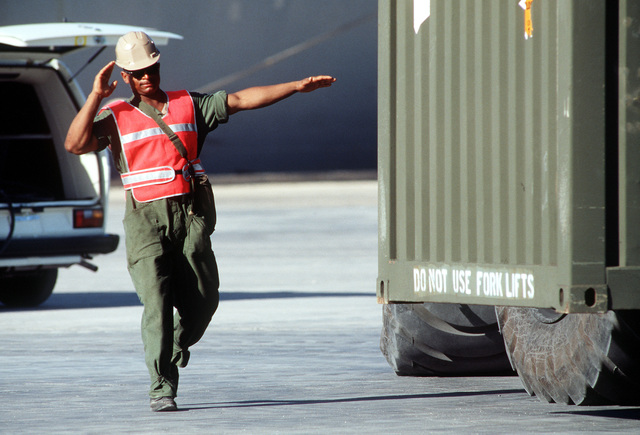A soldier from the 155th Transportation Company guides the driver of a rough-terrain container handler as he moves a container of chemical munitions across the pier during Operation Steel Box. The munitions, which were transported to Johnston Atoll aboard a Military Sealift Command ship, will be taken to the U.S. Army Chemical Activity on the atoll for storage and disposal
