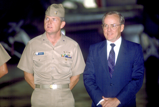 CDR Stephen L. Feeley, left, stands beside Secretary of the Navy H. Lawrence Garrett III as they watch a ceremony during Garrett's stopover at the base