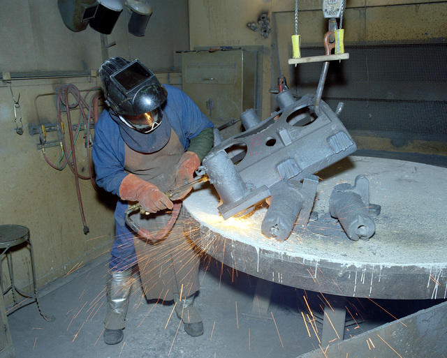Dean Dawson, a civilian employee, uses a cutting torch to remove castings from a subassembly of an M-198 155mm howitzer