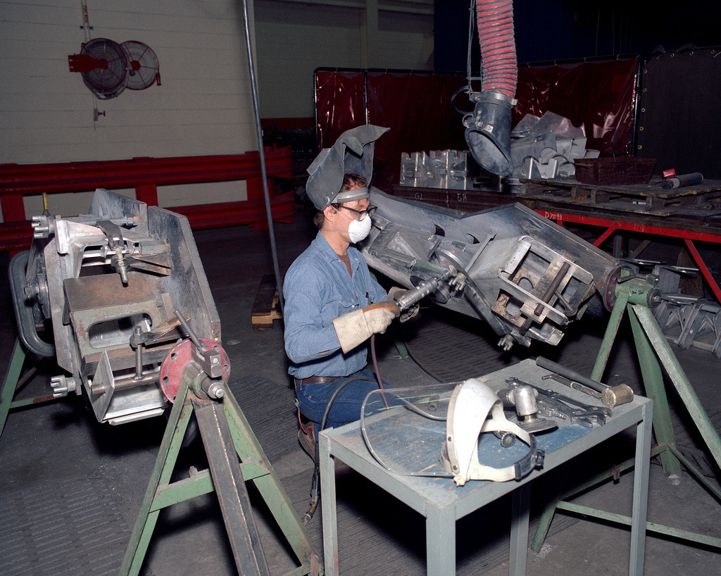 Dwayne Lamp, a civilian employee, grinds down a weld on a subassembly of the top carriage arm for an M-198 155mm howitzer