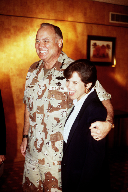 GEN. H. Norman Schwarzkopf, commander in chief, U.S. Central Command, puts his arm around NBC News correspondent Catherine Couric while visiting with members of the media during Operation Desert Storm