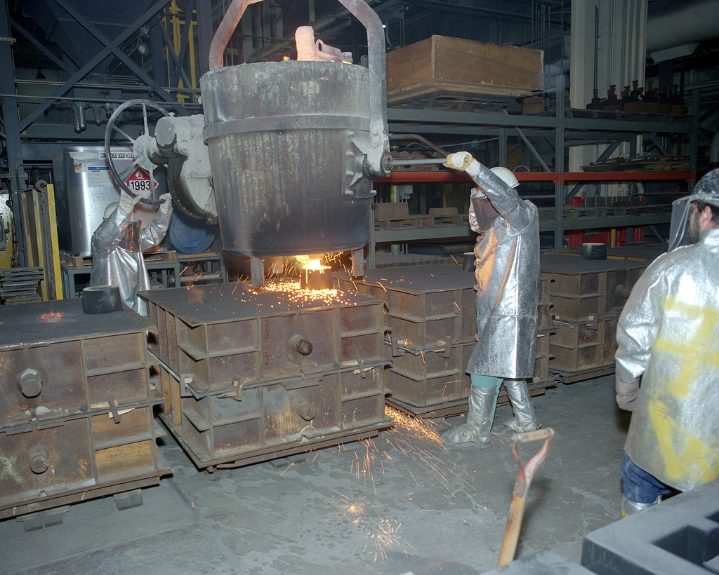 Jeff Ostrand and Everett Olive, civilian employees at the arsenal, pour armor steel castings for an M-198 155mm howitzer in Building 212W