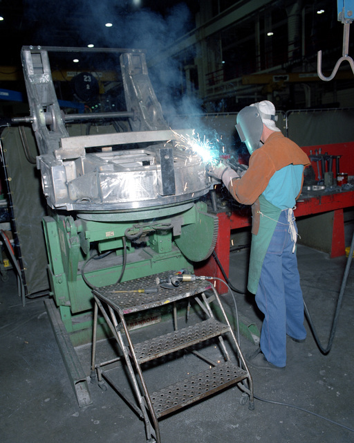 Jerry Whittington, a civilian employee, welds a portion of the M-39 top carriage for an M-198 155mm howitzer in Building 212
