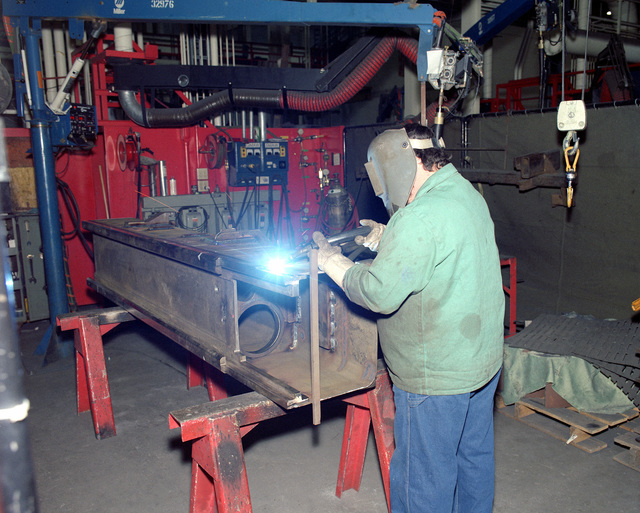 Leo Harvey, a civilian employee, welds a portion of the cradle for an M-198 155mm howitzer in Building 212W