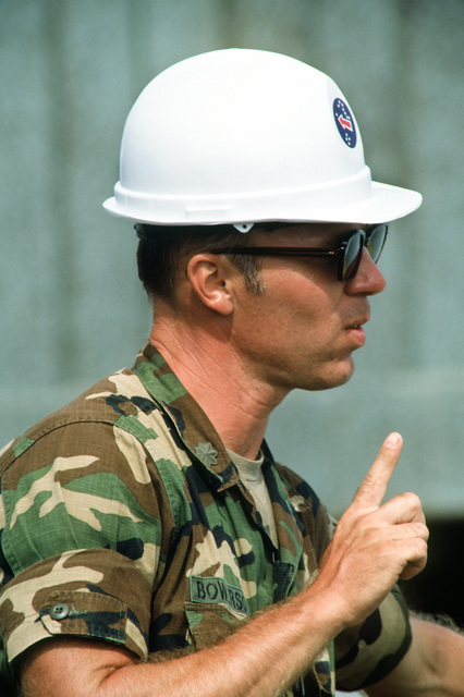 MAJ Tom Bowersox, head of logistics for the U.S. Army Chemical Activity located on the atoll, directs the unloading of chemical munitions from a Military Sealift Command ship during Operation Steel Box. The munitions will be taken to the U.S. Army Chemical Activity on the atoll for storage and disposal