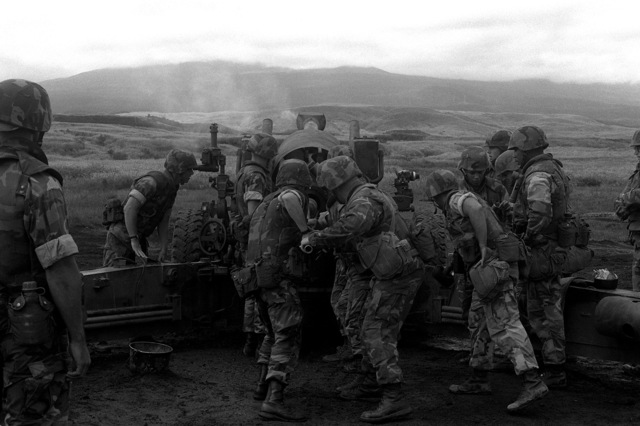 Marines from Marine Wing Support Squadron 171 (MWSS-171), 1ST Marine Aircraft Wing (1ST MAW), load a round into an M-198 155mm howitzer as the gun's crew, five Marines from Btry. B, 1ST Bn., 12th Marines, watches them closely. The Marines from MWSS-171 are at Camp Fuji for battle skills training