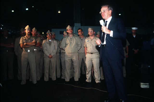 Secretary of the Navy H. Lawrence Garrett III, right, speaks to some of the air facility's officers and enlisted men during a stopover at the base