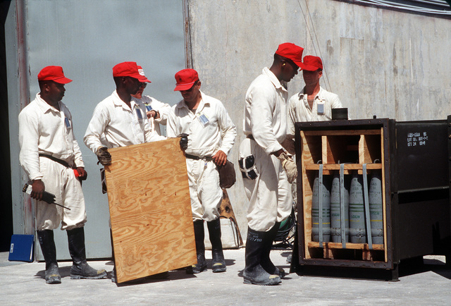 Soldiers prepare to unload a crate of 155mm chemical artillery shells before placing them in a storage bunker during Operation Steel Box. The munitions, which were transported to the atoll aboard Military Sealift Command ships, will be stored in the bunker until their disposal