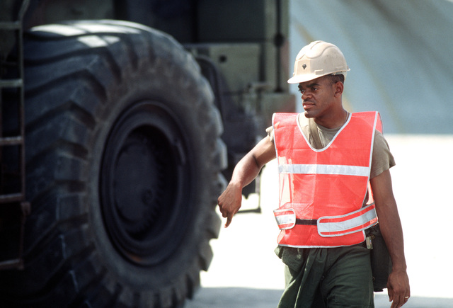 SPC Douglas Megginson of the 155th Transportation Company signals to the driver of a rough terrain container handler as he moves containers of chemical munitions on the pier during Operation Steel Box. The munitions, which were transported to Johnston Atoll aboard a Military Sealift Command ship, will be taken to the U.S. Army Chemical Activity on the atoll for storage and disposal