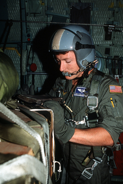 "SRA Paul Stoner, the loadmaster aboard a 345th Tactical Airlift Squadron (345th TAS) C-130 Hercules aircraft, checks a container delivery system box during a ""Tac Trainer"" mission. The 345th TAS deployed to South Korea from Yokota Air Base, Japan to conduct terrain-following navigation and tactical air drop training missions"
