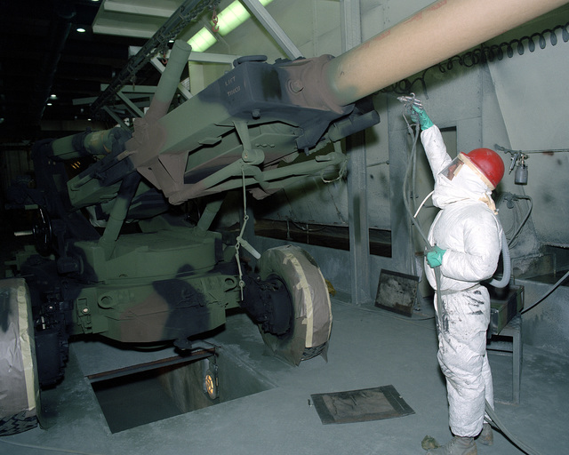 Toby Brown, a civilian employee, applies a coat of paint to the barrel of an M-198 155mm howitzer in the paint booth in Building 208