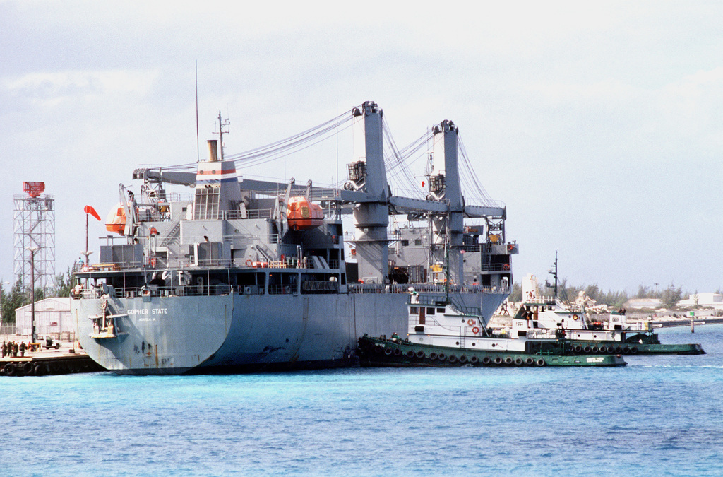 Tug boats push the Military Sealift Command auxiliary crane ship GOPHER STATE (T-ACS-4) into its place at the pier during Operation Steel Box. The ship is delivering chemical munitions to the U.S. Army Chemical Activity on the atoll for storage and disposal