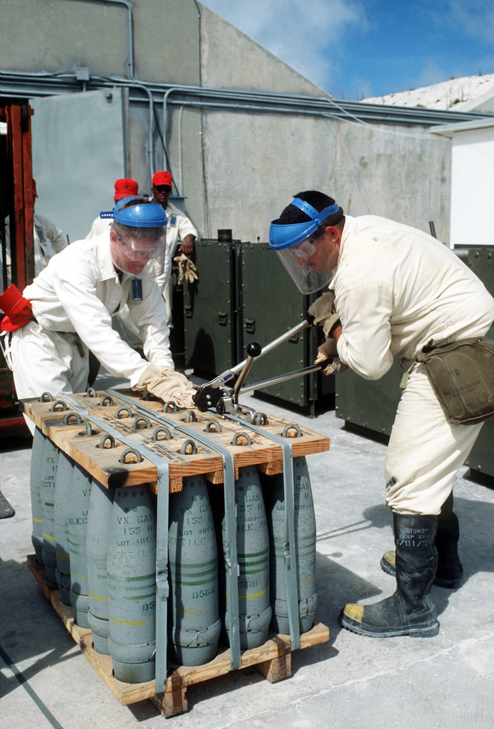 Two soldiers cut the bands on a pallet of 155mm chemical artillery shells before placing them in a bunker during Operation Steel Box. The munitions, which were transported to the atoll aboard Military Sealift Command ships, will be stored in the bunker until their disposal
