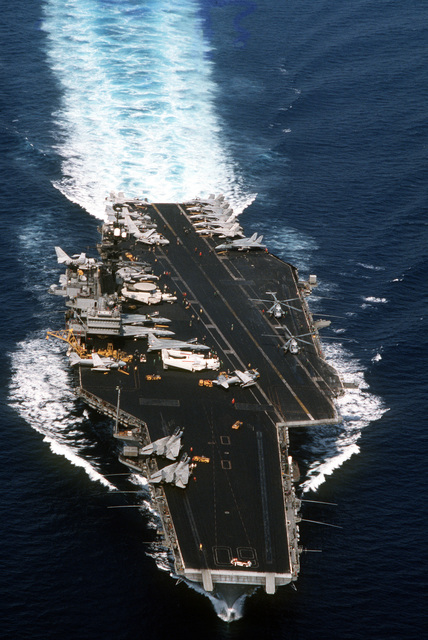 Aerial, bow-on view of the Forrestal Class, Aircraft Carrier USS SARATOGA (CV 60) underway during Operation Desert Shield. Aircraft seen on the deck of the SARATOGA are, F/A-18C as well as are F-14A Tomcats and A-6E Intruders. Also seen are two CH-53D Sea Stallions on the port side of the flight deck