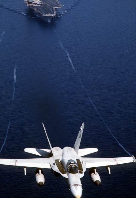 An aerial view of a F/A-18C Hornet aircraft of Strike Fighter Squadron Seventy-Four (VFA-74) climbs out over the Forrestal Class, Aircraft Carrier USS SARATOGA (CV 60) during Operation Desert Shield