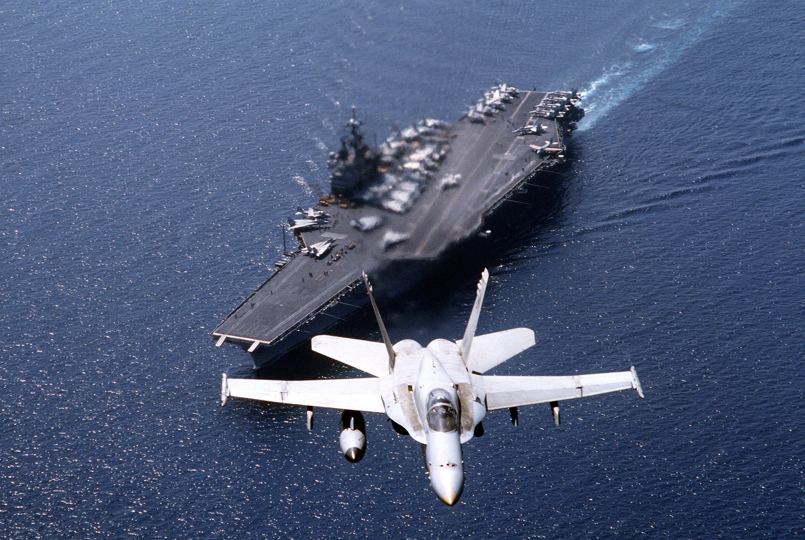An aerial view of a F/A-18C Hornet aircraft of Strike Fighter Squadron Seventy-Four (VFA-74) in flight over the Forrestal Class, Aircraft Carrier USS SARATOGA (CV 60) during Operation Desert Shield. Other F/A-18Cs as well as F-14A Tomcats and A-6E Intruders are seen aboard the flight desk of the SARATOGA