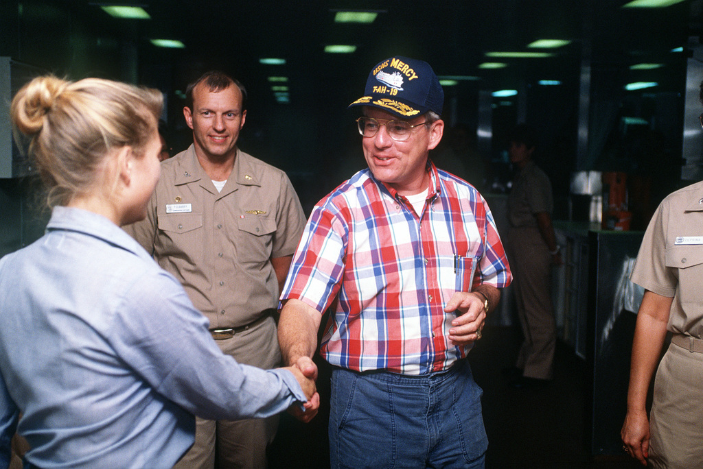 Secretary of the Navy H. Lawrence Garrett III shakes hands with crew members of the Military Sealift Command hospital ship USNS MERCY (T-AH-19) while visiting the ship during Operation Desert Shield
