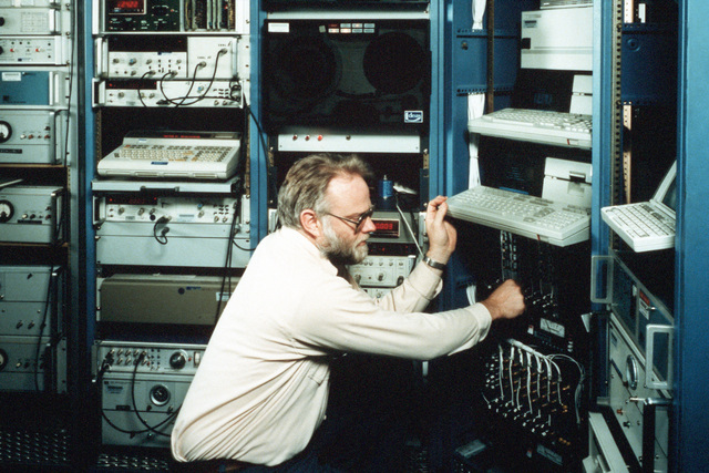 Al Gifford checks a cable on the phase time measurement system in the Clock Test Facility at the Naval Research Laboratory (NRL). The system measures the absolute phase of 48 clocks simultaneously and 900 analog signals per hour
