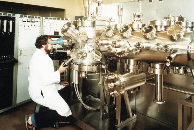 Stuart Wolf observes crystal layering in the Electron Beam Epitaxy Facility at the Naval Research Laboratory (NRL). The crystals are used by scientists at the facility for the development of superconducting lattices
