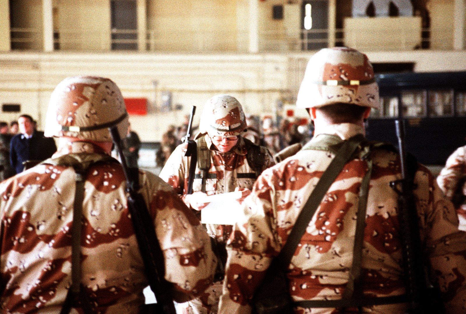 A platoon leader conducts a roll call in a hangar before his