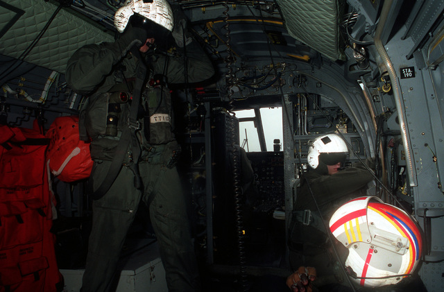 LCPL T. Thomasek, left, the crew chief aboard an HH-46D Sea Knight search and rescue (SAR) helicopter from Headquarters and Headquarters Squadron (H&HS), Marine Corps Air Station, Iwakuni, Japan, checks with his crew during a SAR training flight