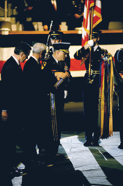 US Army (USA) CHIEF of STAFF General (GEN) Carl E. Vuono prepares to place a battle streamer on the Army Flag during ceremonies at Conmy Hall, Fort Myer, Virginia (VA). With him are (from left) US President George Herbert Walker Bush and Secretary of the Army The Honorable Michael P.W. Stone. The flags were presented by a Color Guard from the USA 3rd Infantry Regiment (The Old Guard)