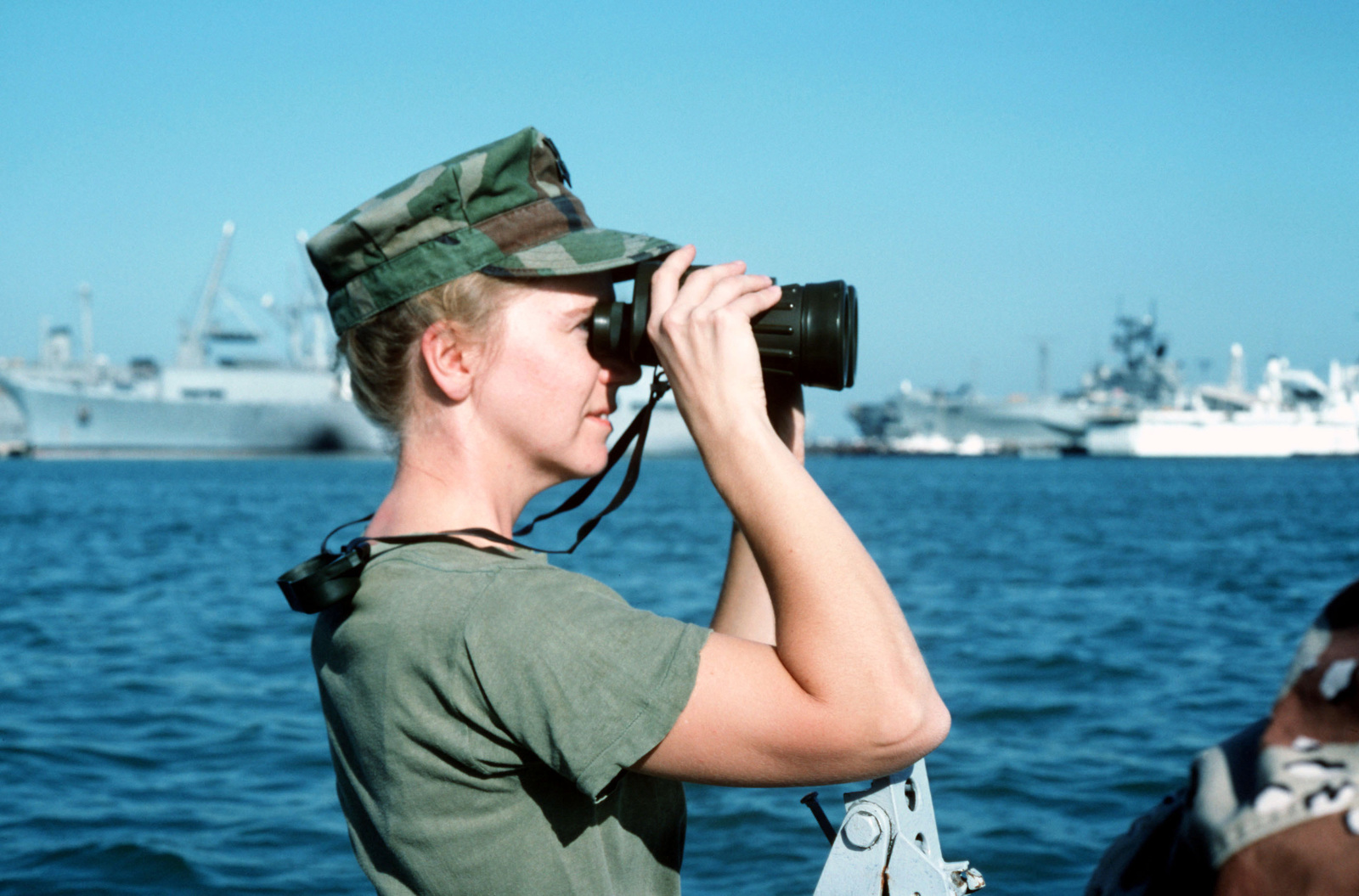 PETTY Officer 1ST Class Cynthia Harvey uses a pair of binoculars to scan the area while on patrol in the harbor. Harvey is a member of the security detachment assigned to the US Navy Administrative Support Unit, Bahrain