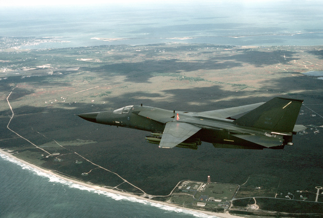 A 509th Bombardment Wing FB-111A aircraft, armed with Mark 82 high drag practice bombs, flies along a coastline