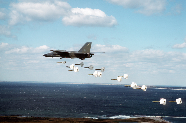 A 509th Bombardment Wing FB-111A aircraft drops Mark 82 high drag practice bombs along a coastline during a training exercise