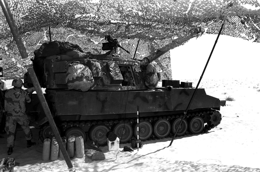 A crewman passes a 155mm projectile into an R Battery, 5th Battalion, 11th Marine Regiment, 1ST Marine Division, 155mm M-109A1 self-propelled howitzer during Operation Desert Shield