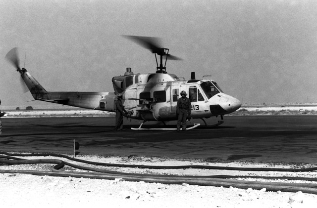 A UH-1N Iroquois helicopter is refueled in preparation for a mission during Operation Desert Storm. An M-2 .50-caliber machine gun is positioned on the side of the helicopter