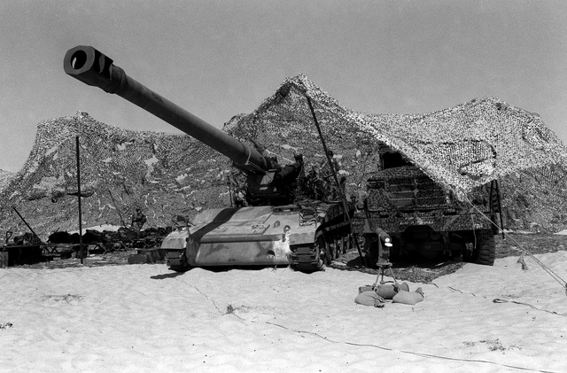 An M-110A2 8-inch self-propelled howitzer of Btry. T, 5th Bn., 5th Marine Regt., 1ST Marine Div., stands beneath camouflage netting in a Marine base camp during Operation Desert Storm