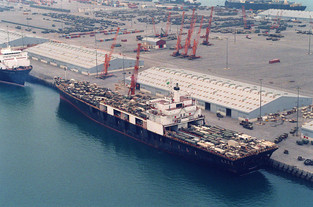 A Military Sealift Command-chartered vehicle cargo ship prepares to offload equipment during Operation Desert Shield