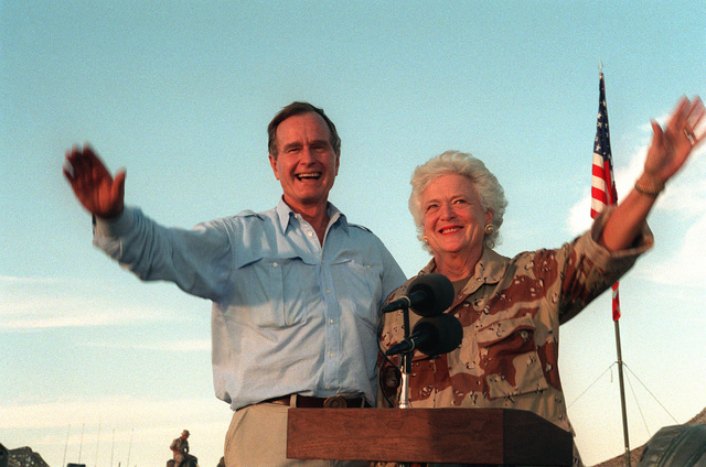 President George Bush and First Lady Barbara Bush wave as they stand in the back of a vehicle during a visit to a desert encampment. The president and his wife are paying Thanksgiving Day visits to U.S. troops who are in Saudi Arabia for Operation Desert Shield. Sen. Robert Dole of Kansas is at left