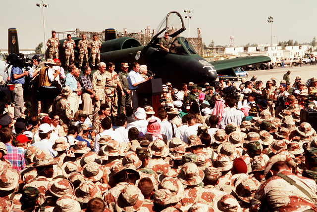 President George Bush, center, speaks to the crowd at an air base while making one of several Thanksgiving Day visits to U.S. troops who are in Saudi Arabia for Operation Desert Shield. The president's wife, Barbara, stands beside him. Sen. Bob Dole of Kansas is at left, facing the crowd; Speaker of the House Rep. Tom Foley is fourth from left. An A-10A Thunderbolt aircraft is in the background
