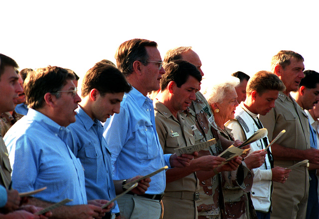President George Bush, fourth from left, attends a prayer service during his visit to the amphibious assault ship USS NASSAU (LHA-4). Among those accompanying the president is his wife, Barbara, fourth from right. The president and his wife are paying Thanksgiving Day visits to U.S. military personnel deployed to the Persian Gulf region for Operation Desert Storm