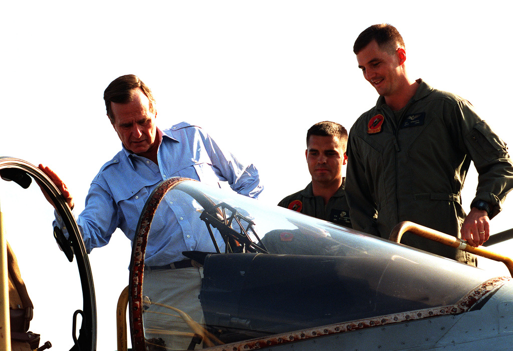 President George Bush looks in the cockpit of a Marine Attack Squadron 331 (VMA-331) AV-8B Harrier aircraft during his visit to the amphibious assault ship USS NASSAU (LHA-4). The president is paying Thanksgiving Day visits to U.S. military personnel deployed to the Persian Gulf region for Operation Desert Shield
