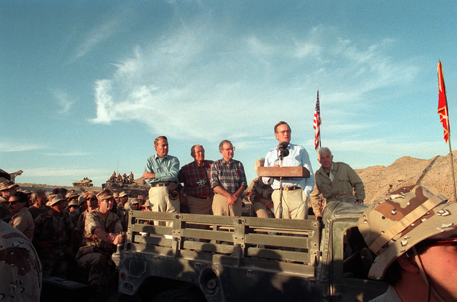 President George Bush, second from right, stands in the bed of an M998 High-Mobility Multipurpose Wheeled Vehicle (HMMWV) to address the Marines and Seabees at a desert encampment. The president and his wife are payilng Thanksgiving Day visits to U.S. troops who are in Saudi Arabia for Operation Desert Shield. Sen. Robert Dole of Kansas is at left