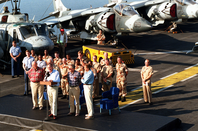 President George Bush stands at the podium as he makes some remarks during his visit to the amphibious assault ship USS NASSAU (LHA-4). The president is paying Thanksgiving Day visits to U.S. military personnel deployed to the Persian Gulf region for Operation Desert Shield. Sen. Robert Dole of Kansas is on the platform at right