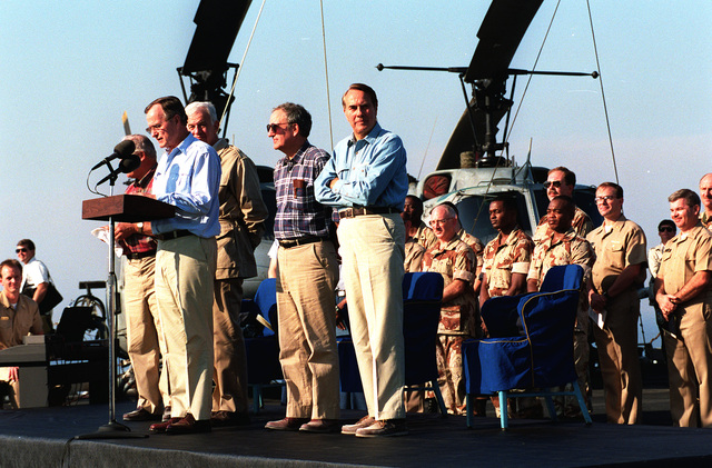 President Georger Bush makes some remarks during his visit to the amphibious assault ship USS NASSAU (LHA-4). The president is paying Thanksgiving Day visits to U.S. military personnel deployed to the Persian Gulf region for Operation Desert Shield. Sen. Robert Dole of Kansas is on the platform at right