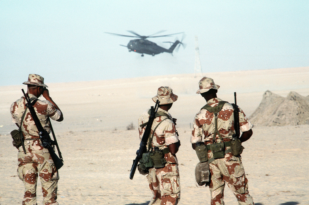 Three Marines watch as a CH-53E Super Stallion helicopter comes in for a landing during Operation Desert Shield