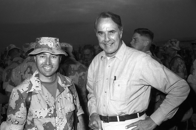Sen. Robert Dole pauses for a photograph with CHIEF Warrant Officer 2 Adao, the 1ST Marine Division's photo officer, while paying a Thanksgiving Day visit to the 1ST Marine Division Combat Operations Center (COC) during Operation Desert Shield.