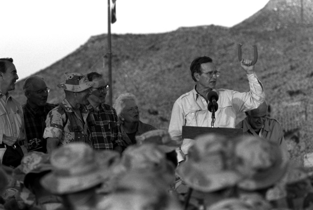 With his wife, Barbara, beside him, President George Bush holds up a horseshoe as he speaks from the back of a truck during his Thanksgiving Day visit to the lst Marine Division combat operations center (COC) during Operation Desert Shield. Also on the truck are Sen. Robert Dole, left, and Speaker of the House Tom Foley, right.